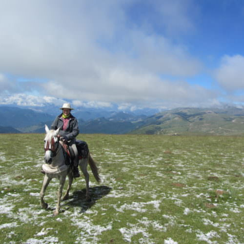 Adventurous trail riding holiday through Pyrenees Mountains, Spain. Horse, snow, spectacular views, blue skies.