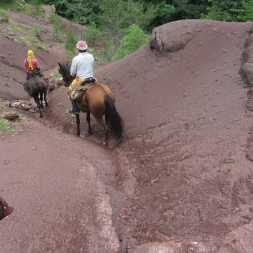 Adventurous trail riding holiday through the Pyrenees Mountains, Spain. Riders and horses, steep trail